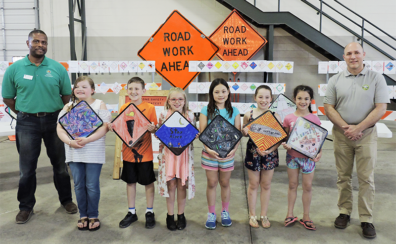 Steve Thomas (left), Superintendent of KCRC's South Complex, and John Gorney, Director of Kentwood Public Works Department, present awards to six of the nine poster contest winners: (from left) Aubrey Garcia, Kenan Music, Vaelyn Moore, Evie Partridge, Brooklyn Brugnoli and Carmen Cooke. (not pictured: Ellerie Shoemaker, Rowen Smith and Shelby Searcy)
